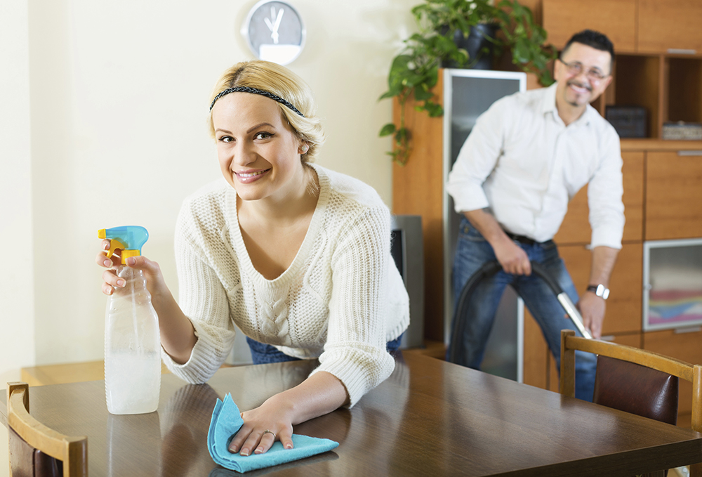 Positive young spouses dusting and hoovering at domestic interior
